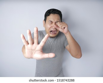 Portrait of funny young Asian man crying and showing surrender gesture, hands raised up asking to stop bully on him, against grey wall