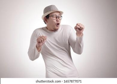 Porträt eines lustigen jungen Asiaten, der glücklich lächelt und tanzt, freudig und fröhlich die gute Erfolgsgestalt der Nachrichten ausdrückt