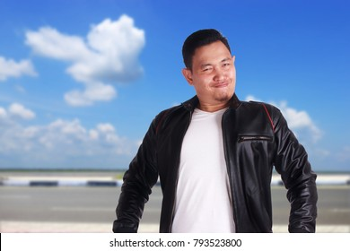 Portrait of funny young Asian wearing black leather jacket over confident gesture, over cloudy blue sky background