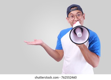 Portrait of funny young attractive Asian man shouting with megaphone while showing something on his open palm hand, happiness excited calling people promotion concept, empty copy space template