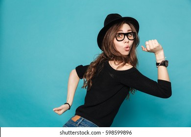 Portrait of a funny young cute girl in hat running isolated on the blue background