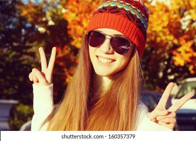 Portrait of a funny young girl in the autumn weather in warm clothes and hat.
