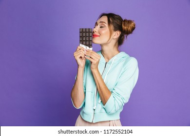 Portrait of a funny young girl with bright makeup over violet background, smelling chocolate bar