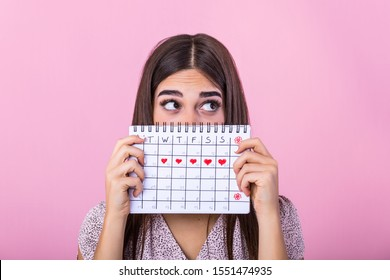 Portrait of a funny young girl in hiding behind a menstrual periods calendar and looking away at copy space isolated over pink background. Female Period calendar
