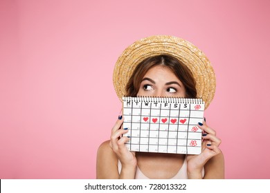 Portrait of a funny young girl in summer hat hiding behind a periods calendar and looking away at copy space isolated over pink background