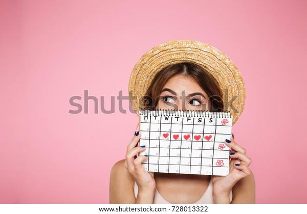 Retrato de una jovencita divertida en un sombrero de verano escondiéndose detrás de un calendario de periodos y mirando lejos el espacio fotográfico aislado sobre fondo rosa