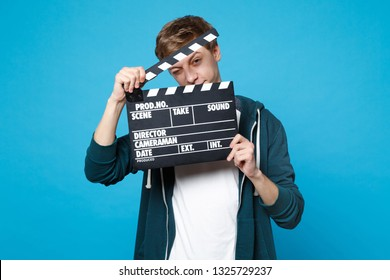 Portrait of funny young man in casual clothes holding classic black film making clapperboard isolated on blue wall background in studio. People sincere emotions lifestyle concept. Mock up copy space