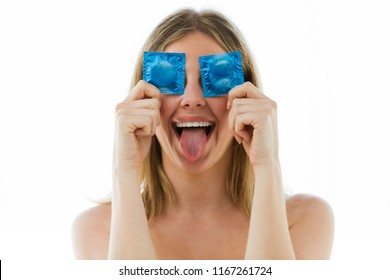 Portrait of funny young woman covering eyes with condoms over white background.