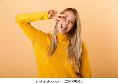 Portrait of a funny young woman dressed in sweater standing isolated over yellow background, showing peace gesture