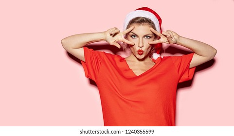 Portrait of funny young woman fooling around and showing peace sign. Christmas concept. Studio picture of pretty girl wearing santa hat and posing on pink background