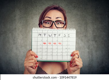 Portrait of a funny young woman in glasses hiding behind a periods calendar and looking at camera isolated gray wall background