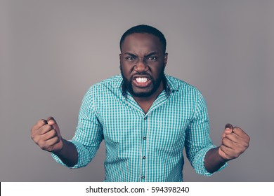 Portrait of furious angry afroamerican man in rageand screaming and showing fists