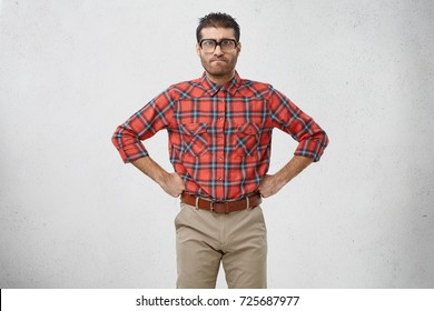 Portrait of furious bearded dark haired man geek looking ridiculous in old fashioned rectangular eyeglasses with thick lenses having serious or angry facial expression, keeping hands on his waist