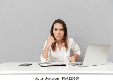 Portrait of a furious young business woman sitting at the office desk and showing her fist isolated over white background