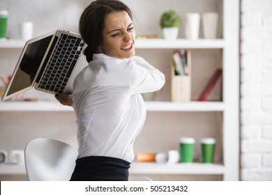 Portrait of furious young woman about to throw and break her laptop at workplace. Stress concept