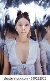 Portrait of futuristic scared young woman. Reflection of our mind and soul concept. Beautiful young multi-racial asian caucasian model cyber girl in silver urban clothes with conceptual hairstyle and