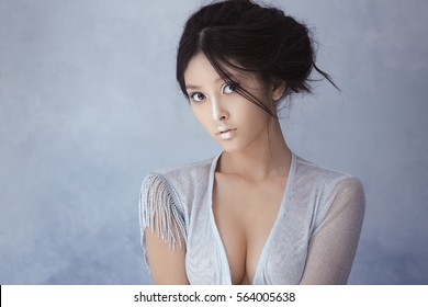 Portrait of futuristic sensual sexy young woman. Beautiful young multi-racial asian caucasian model cyber girl in silver urban clothes with conceptual hairstyle and make-up against blue textured copy