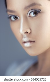 Portrait of futuristic young woman close-up. Beautiful young multi-racial Asian Caucasian model cyber girl in silver urban clothes with conceptual hairstyle and make-up against blue copy-space