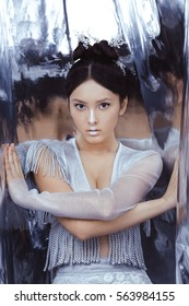 Portrait of futuristic young woman. Reflection of our mind and soul concept. Beautiful young multi-racial asian caucasian model cyber girl in silver urban clothes with conceptual hairstyle and make-up