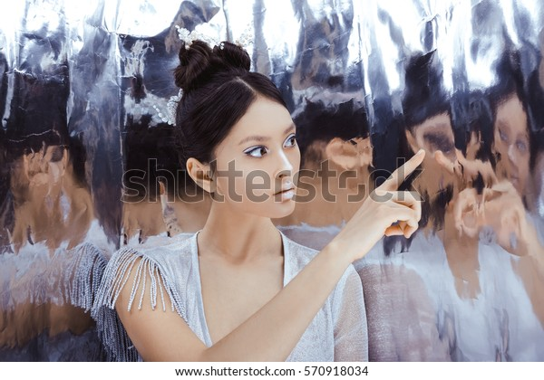 Portrait of futuristic young woman touching reflection in mirror. Reflection of our mind and soul concept. Beautiful young multi-racial asian caucasian model cyber girl in silver urban clothes with