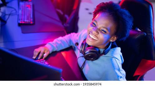 Portrait Gamer African American beautiful woman play online games computer, streamer neon room banner.