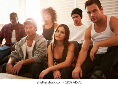 Portrait Of Gang Members Sitting On Sofa In House