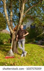 portrait of a gardener relaxing and leaning on a tree