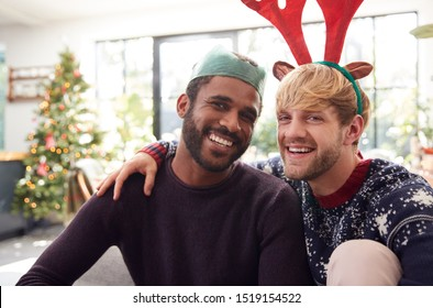 Portrait Of Gay Male Couple At Home Wearing Fancy Dress Antlers And Paper Hat On Christmas Day