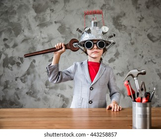 Portrait of geek child pretend to be businessman. Funny kid with toy virtual reality headset in modern loft office. Success, creative and innovation technology concept. Copy space for your text