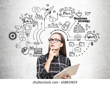 Portrait of a geek girl in glasses standing near a concrete wall with a copybook and a business strategy icons drawn on it