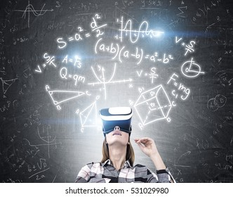 Portrait of a geeky girl wearing virtual reality glasses and looking upwards while standing near a blackboard with formulas