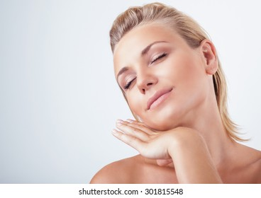 Portrait of gentle calm girl with closed eyes and hand near face over light background, natural skin care, perfect complexion, enjoying day spa