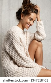 Portrait of gentle smiling girl with nice tan skin wearing snow white knit dress. Sensual young woman with tied up hair sitting hugging knee and looking down