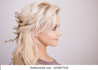 Portrait of gentle young woman with blond hair. Trendy hairstyle, natural hair styling