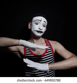 Portrait of gesticulating mime on black background