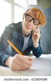 Portrait of ginger creative man working at blueprints, drawing  on paper while speaking on phone and smiling cheerfully at workplace