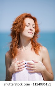 Portrait of ginger girl with loose hair and eyes closed sunbathing at the sea. Red haired young woman poses hiding her nudity under beach towel