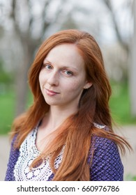 Portrait of ginger girl outdoors. Red haired young woman looking at camera smiling