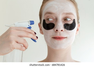 Portrait of ginger woman with black eye patches and white mask showing how is necessary to moisturize the skin. Spray bottle