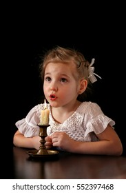 Portrait of a Girl 4-5-6 years, looking at the burning candle isolated on black background.