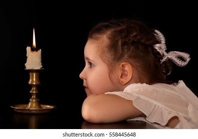 Portrait of a Girl 4-5-6 years, looking at the burning candle isolated on black background