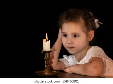 Portrait of a Girl 4-5-6 years, looking at the burning candle isolated on black background. Make a wish