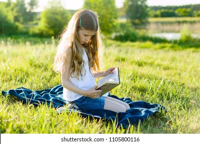 Portrait of a girl 8 years old on green meadow. Child reads book, background sunset rustic landscapes.