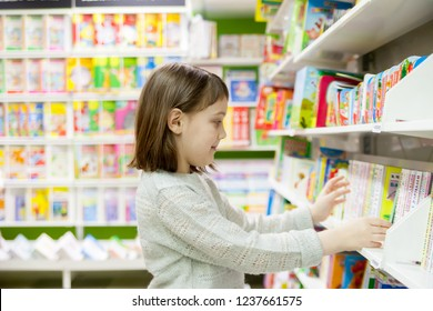 Portrait of   girl  of 8   years in shop choosing books in   bookstore