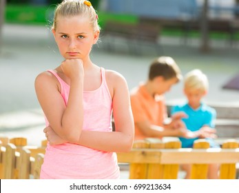 Portrait of girl 8-11 years old which is taking offense on her friends in the park.
