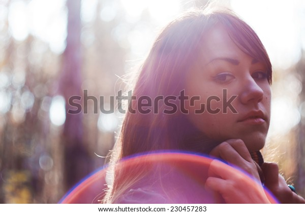 Portrait of girl in backlight. Beautiful brunette. Sun's rays and glare. White background