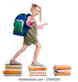 Portrait of girl with backpack walking from top to top of book piles