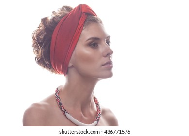 Portrait of a girl with beaded ornaments in red turban on a white background