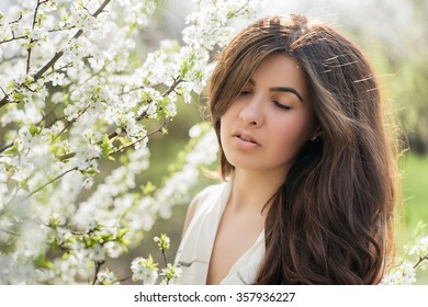 Portrait of a girl with beautiful hair in the lush spring garden, beauty, makeup, hair,