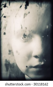 Portrait of the girl behind dirty glass